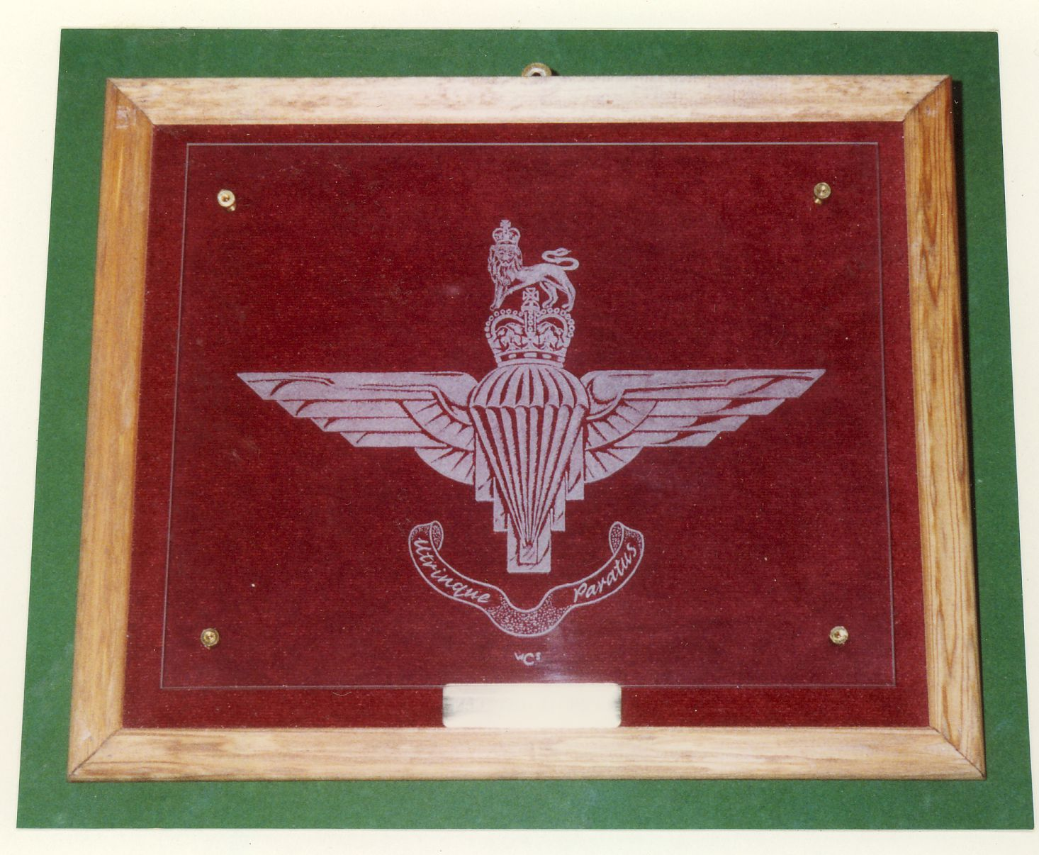 An engraving of the badge of the Parachute Regiment. On this occasion it is mounted above a maroon velvet background.