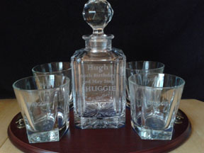 Four personal engraved crystal whisky glasses and decanter in the middle. These are sat on a polished wooden base.