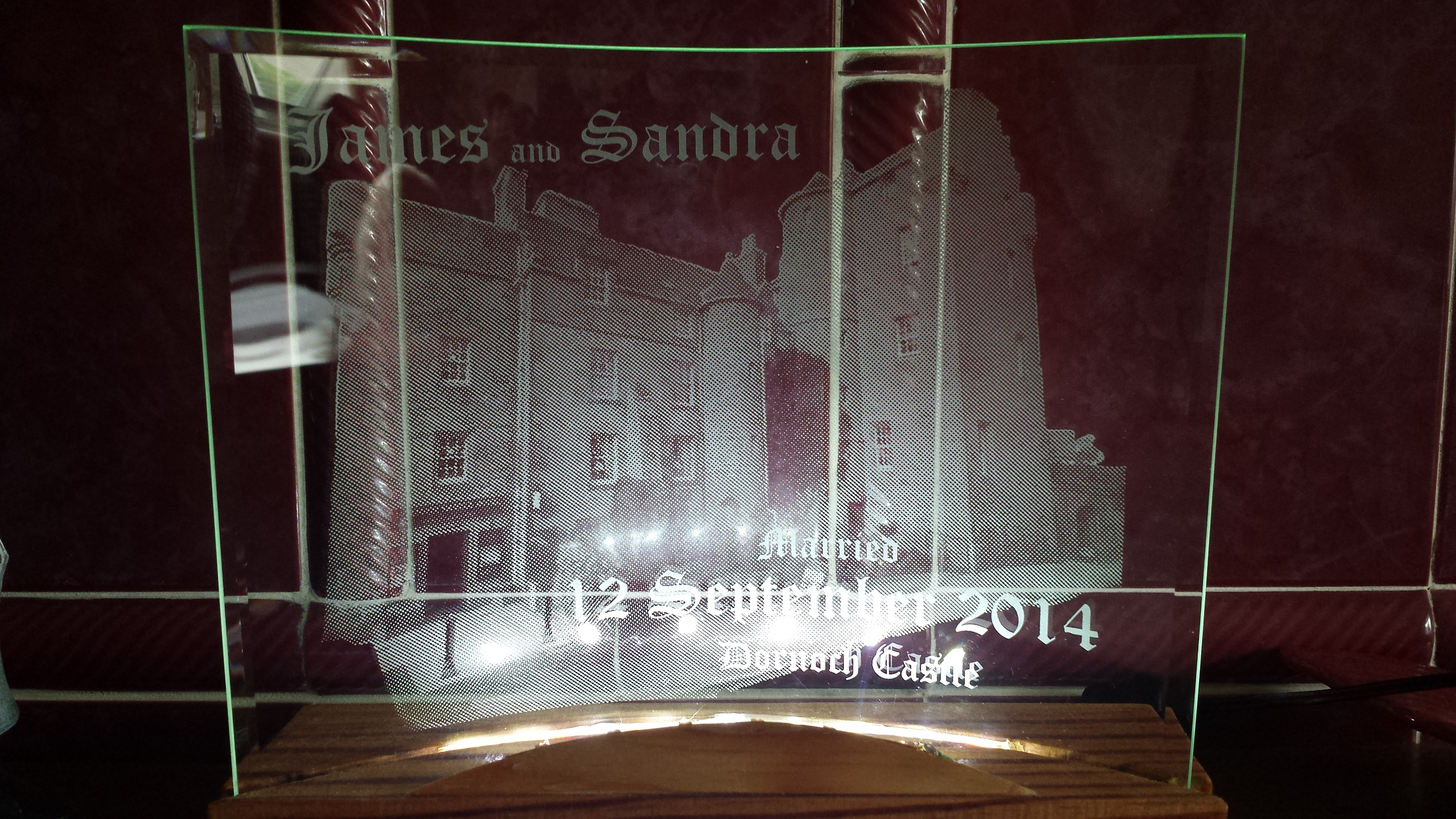 This is a picture engraving of the Dornoch Castle hotel directly onto the back of a piece of curved glass.On the front of the glass is engraved James and Sandra and the date and location of the marriage. Engraved in this manner creates depth of field and gives a 3D effect.