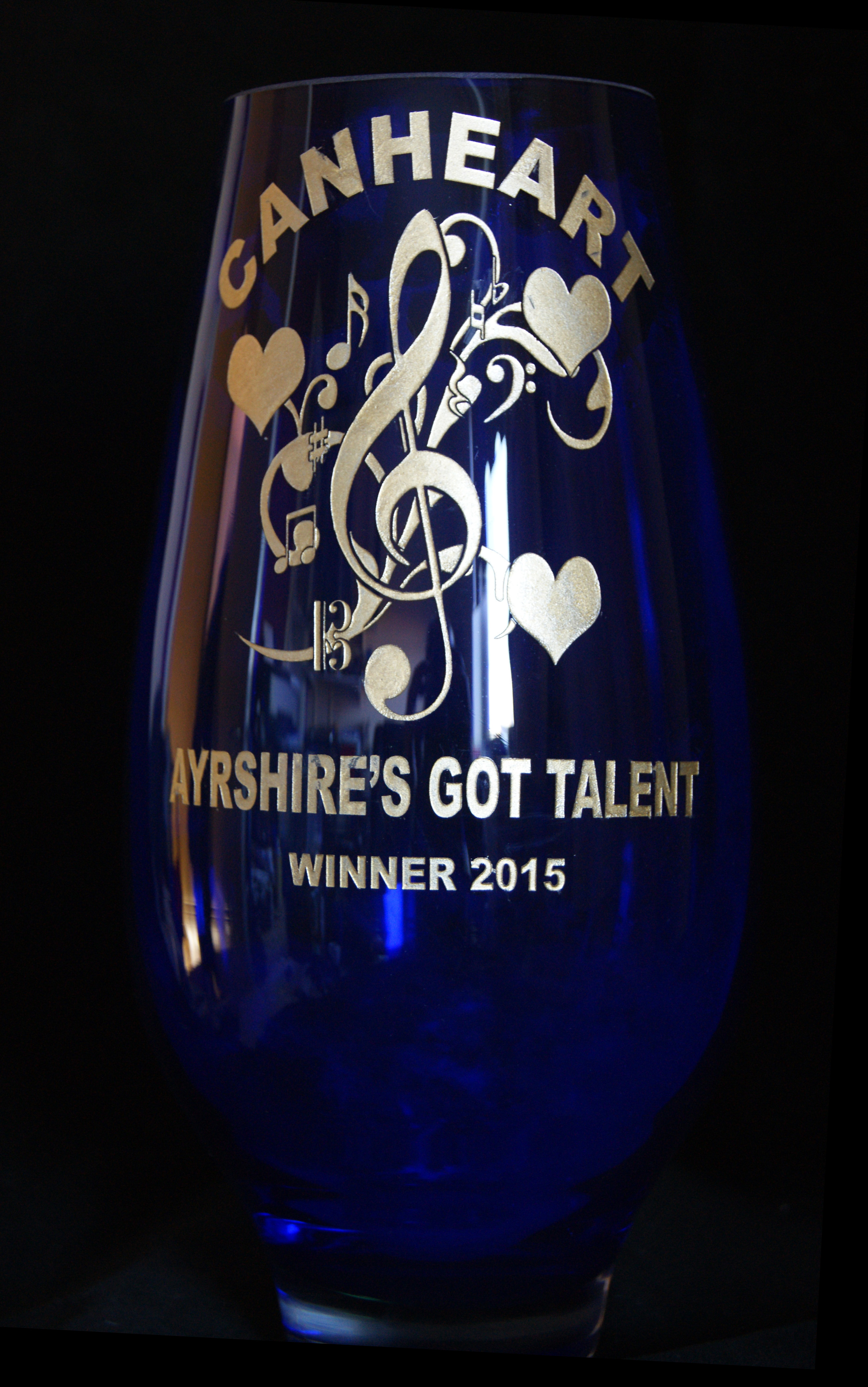 A deep blue vase with the CANHEART logo and Ayrshire's Got Talent engraved then infilled with gold