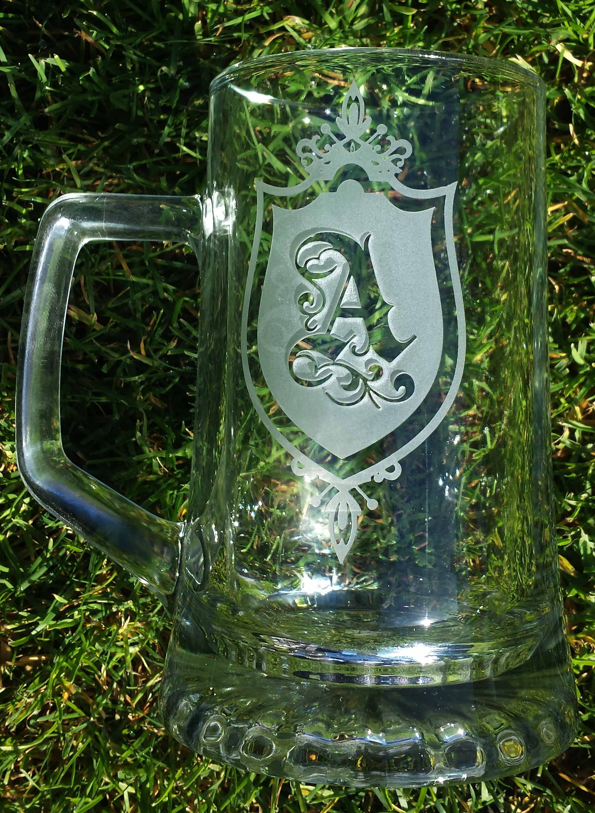 This is a pint glass engraved very deeply around a monogrammed A giving the A the look of being high above the surface of the Glass.