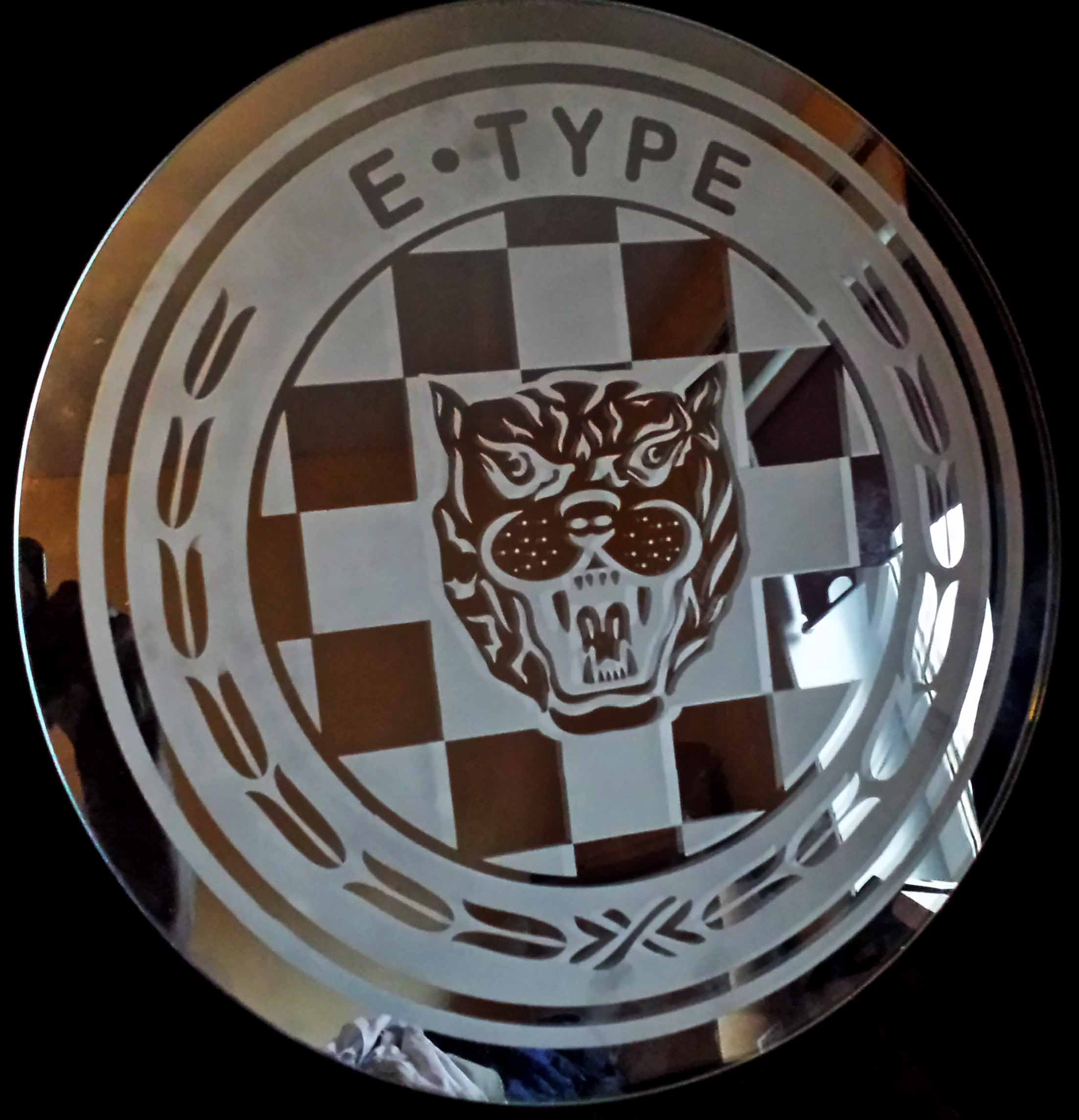A round piece of safety glass 22 inch in diameter engraved with the E Type Jaguar logo.